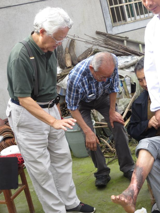 照片十三 賀英明與Peter細察治癒後患者之腳部