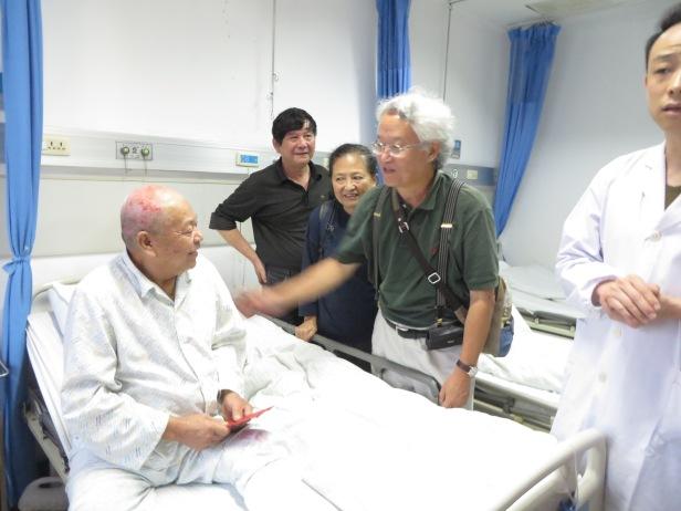 照片十二 賀英明慰問正在治療中的爛腳病患者。王選與吳建平也在旁